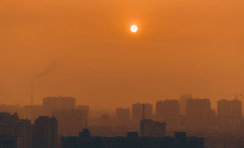 Orange glow at sunset in polluted city.